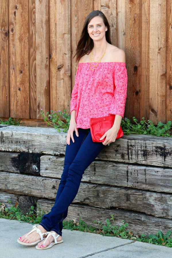 Red off-the-shoulder shirt paired with dark blue jeans.